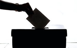 image of hand placing a piece of paper in a box