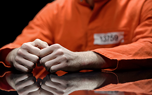 inmate sitting at a table, hands clasped